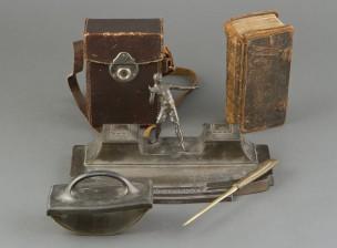 Kirjoituspöytäteline, kamera ja virsikirja